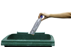 Female hand throwing empty plastic bottle into the trash. Female hand throwing a plastic bottle into the trash, white background Royalty Free Stock Images