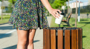 Female hand throwing paper cup on trash in park Royalty Free Stock Images