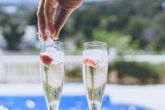 Female hand throws ice into a glasses champagne with strawberry inside on sunny terrace overlooking swimming pool at stock photo