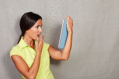 Female with hand to mouth looking at tablet Royalty Free Stock Photos