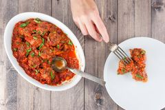 Female hand to take the peace of meatball with tomato sauce from Stock Images