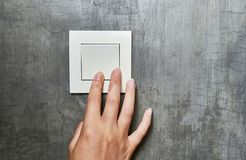 Female hand, to turn off the light, switch, front view.  stock photo