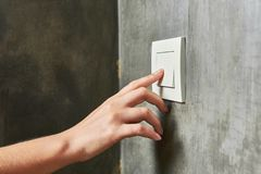 Female hand, to turn off the light, switch, front view.  stock photos