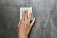 Female hand, to turn off the light, switch, front view.  stock photography