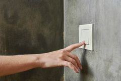 Female hand, to turn off the light, switch, front view.  stock image