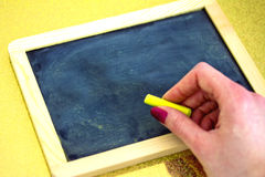 Female hand about to write on blackboard. Hand writing on blackboard with yellow chalk, insert your text Stock Images
