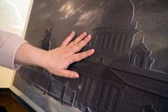 Female hand touches a special relief picture for the visually impaired