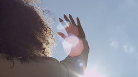 Female hand touching blue sky and raising to sun. stock footage