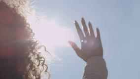 Female hand touching blue sky and raising to sun.