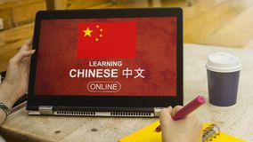 Female hand is touching a chinese symbol screen tablet computer. Gadget and the hand is writing on the yellow notebook with the cup of coffee at the library stock photography