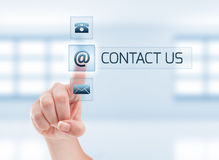 Female hand touching contact us button. Futuristic contact us concept on light blue Royalty Free Stock Photography