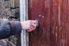 Female hand touching and feeling a knob. A female hand is touching and feeling a nice old knob on a rustic door Stock Image