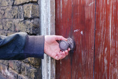 Female hand touching and feeling a knob. A female hand is touching and feeling a nice old knob on a rustic door Stock Photos