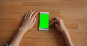 Female hand touching green mock-up smartphone screen lying on wooden table. Female hand is touching green mock-up smartphone screen lying on wooden table in stock video
