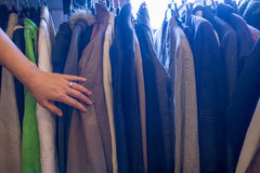 Female hand touching male jackets on rack Royalty Free Stock Photo