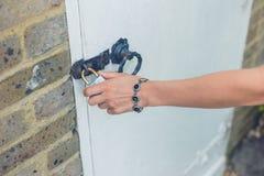 Female hand touching padlock outside Royalty Free Stock Photos
