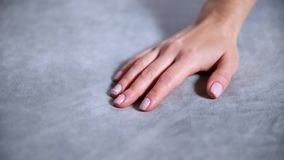 Female hand touching soft and clean grey blanket.