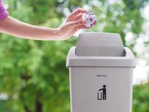 female hand trowing a paper into a garbage bin on bokeh background. cleaning concept. royalty free stock photo
