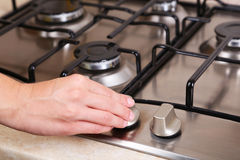 Female hand turn on gas stove. Royalty Free Stock Photo