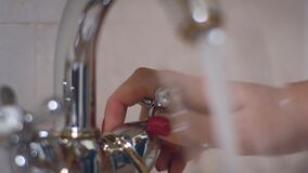 Female hand turning knob on tap and pouring water into glass in bath room. Female hand turning knob on kitchen faucet and pouring water into glass in bath room stock footage