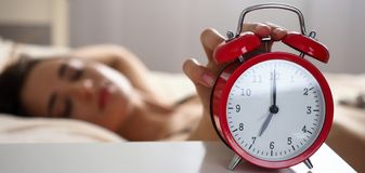 Female hand turning off disturbing noisy alert from red alarm clock. Letterbox view of female hand turning off disturbing noisy alert from red alarm clock royalty free stock image