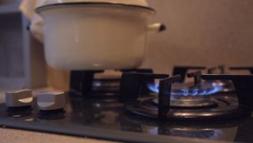Female hand turns on gas stove in dirty budget kitchen with dim light stock video footage