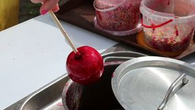 Female hand turns red apple on stick in syrup stock video footage