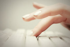Female hand typing on computer keyboard Stock Photo