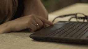 Female hand typing on keyboard notebook to write letter by email close up