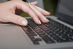 Female hand typing on a laptop keyboard Royalty Free Stock Images