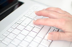 Female hand typing on a white keyboard Stock Photo