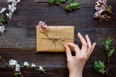 Female hand unpacking gift box wrapped with craft paper and flowers on the wooden table top view. Gift for any holiday.  stock image