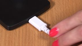 Female hand unplug white micro usb cable to smart phone. Extreme closeup shot. 4K stock footage