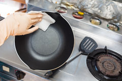 Female hand use white fabric cleaning pan. Stock Photos