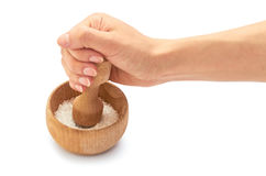 Female hand use wooden mortar with sea salt for cooking. Isolated on white background Stock Photos