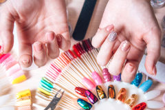Nail art concept. Woman making decoration on the nails on white table Stock Images