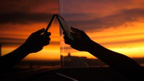 Female hand uses smart phone on a city background of sunset in the reflection of the window. Female hand uses smartphone on a background of sunset in the Stock Images