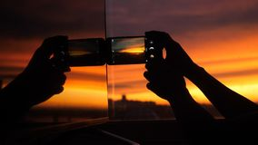 Female hand uses smart phone takes picture on a city background of amazing sunset in the reflection of the window. Female hand uses smart phone takes picture on Royalty Free Stock Image