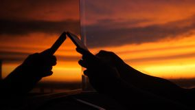 Female hand uses smart phone on a city background of sunset in the reflection of the window. Female hand uses smartphone on a background of sunset in the Royalty Free Stock Photos