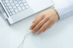 Female hand using computer mouse. Female hand using mouse and laptop computer Stock Image