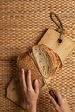 Female hand using long knife cutting bread on wood block showing air flour texture. stock images