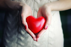 Female hand valentine heart. Object red heart-shaped hands holding a young person stock image