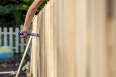 Female hand varnishing a wooden fence stock photos