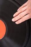 Female hand on vinyl record Stock Photos