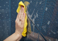Female hand washes the blue tile on the wall Stock Photos