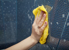 Female hand washes the tile on the wall with a cloth lather Stock Photography