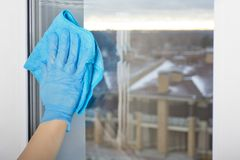 Female hand washes a window of blue cloth,. Female hand in the economic glove washes a window of blue cloth,the views of low-rise houses Stock Photography