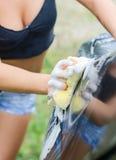 Female hand washing car. Royalty Free Stock Image