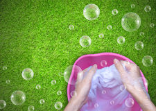 Female Hand washing clothes in the pink basin with clear Bubble. Soap Stock Image