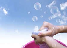 Female Hand washing clothes in the pink basin with clear Bubble. Soap against blue sky Royalty Free Stock Photos